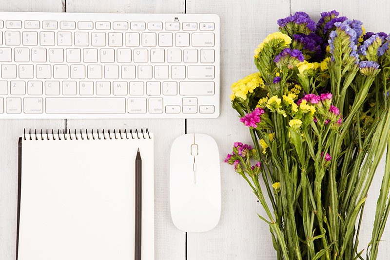Wireless slim keyboard, mouse, notepad with pencil and colorful flowers on white wooden table